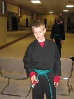 A young man with the rank of green belt.
