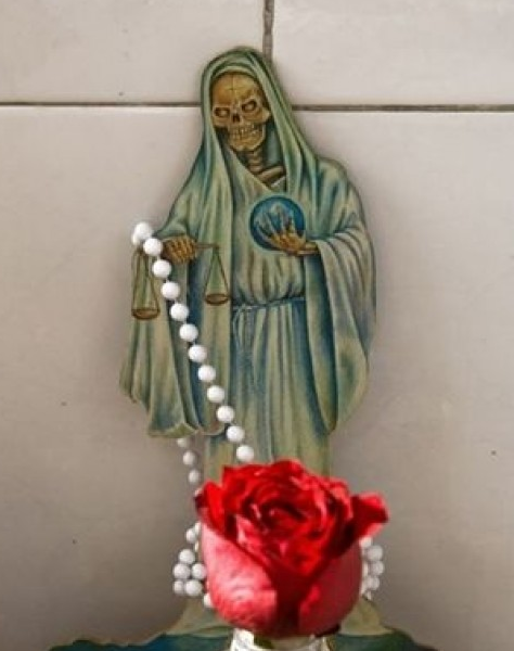 Santa Muerte is a skeleton adorned in ornate robes and with a scythe. Many worshipers sees in her the face of a variety of Our Lady.
