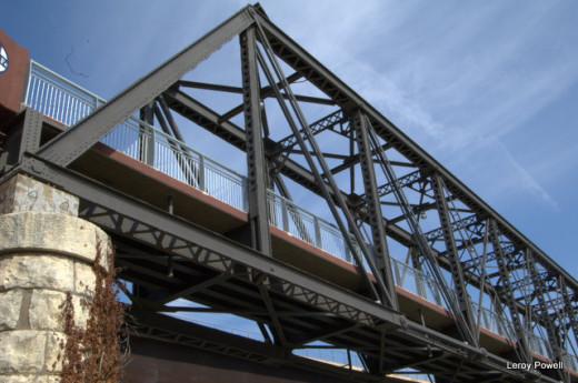 A pedestrian bridge that incorporates an older rail line into its construction.