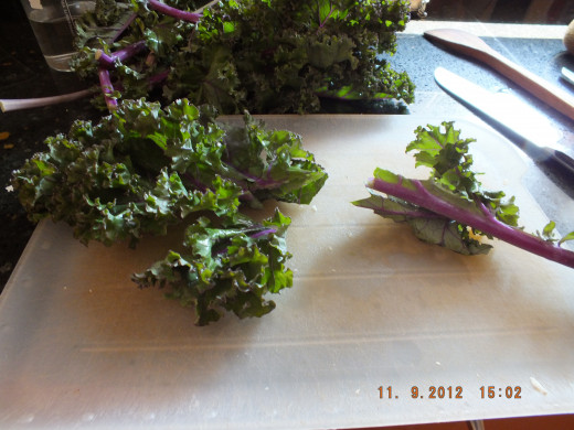 Stripping the kale off the thick stalk. Then chopping it into bite size pieces.