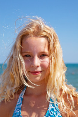 A young blonde in bright sunlight with a shadow cast on her face. Fill-in light techniques could be used to further eliminate the shadows even at the expense of the background. Nonetheless, the shadows are not much of a big deal in this photo.