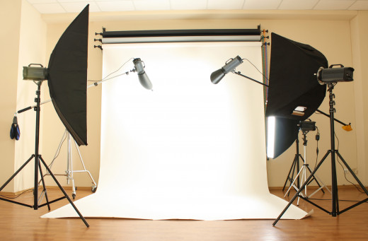 An empty photo studio with lighting equipment and a white backdrop.