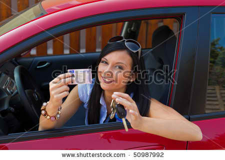 Young lady showing off her driver's license and car keys