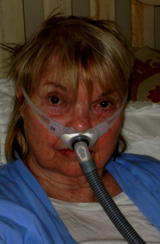 In bed wearing the C-Pap that delivers oxygen during sleep.