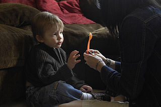 Three-year-old Joey Adams reaches for a fork after correctly identifying the utensil to Board Certified Behavior Analyist (BCBA) therapist Kenna Nelson during an in-house therapy session.