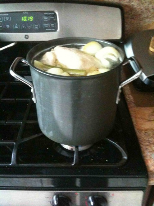 Whole chicken cooking in a pot of water with onion, carrot, and celery stalks