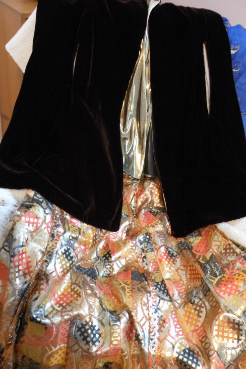 A long skirt with metallic patterns goes well with an old velvet cape.