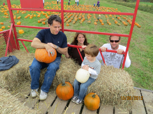 My brother and grandson holding pumpkins; my daughter and son-in-law looking on...this was the hay wagon.