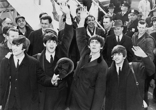 The Beatles wave to fans after arriving at Kennedy Airport. (Date:7 February 1964) (Photo Credit: United Press International)