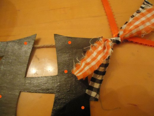 tie strips of material and ribbon in between each letter and on the ends