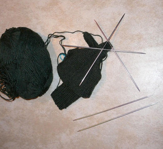 A set of double-pointed knitting needles, in this case being used to knit the finger of a glove