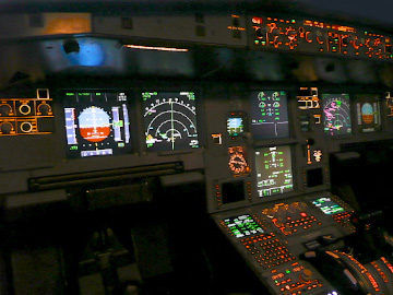 The flight deck instrument panel lit up at night