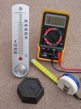 Four metric measuring devices - a tape measure, a thermometer, a one kilogram weight and an electrical multimeter