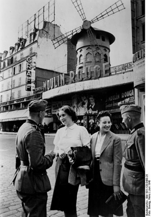 "German soldiers ""hitting"" on local women in front of the Moulin Rouge cabaret, which still exists today, mostly unchanged. Paris, June 1940"