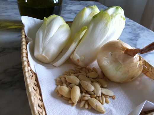 Endives, pine nuts and almonds, onion and extra virgin olive oil mixed and cooked in a pastry (not in the photo) make a simple pie