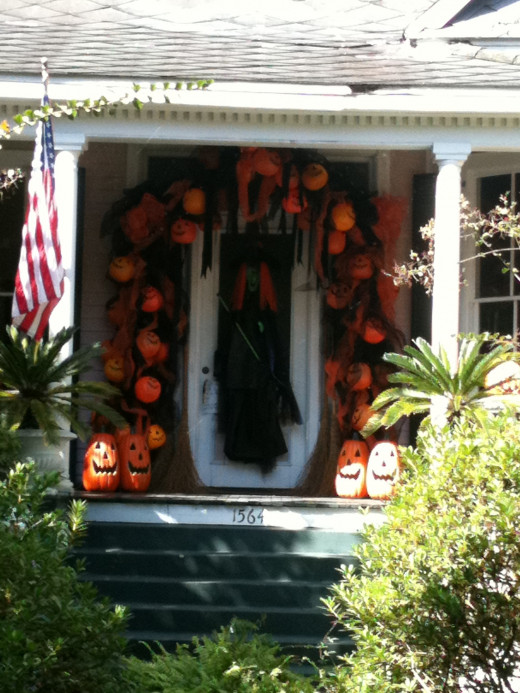 Home on Dauphin Street in Mobile, AL.   There is a base of green fake Christmas garland underneath.  The art mesh is cut into shorter strips and she uses simple orange pumpkins.