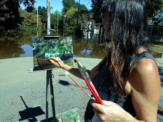 A University art teacher painting on-site.