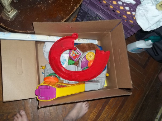 Items that do not belong downstairs are placed back into the box to be carried upstairs.