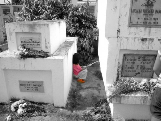 My little niece taking refuge from the scorching sun at my grandparents' resting place.