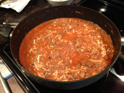 Mix the browned ground beef with spaghetti sauce, mushrooms, water, and the cheeses.
