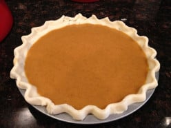 Pinched edges give the crust a pretty look. Pour pumpkin pie filling into the unbaked pie pastry.