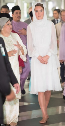 Kate wears white during a mosque visit.  She wears a head covering and takes off her shoes while being shown around the mosque.