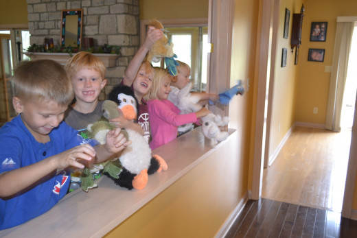 Kids using stuffed animals for a puppet show