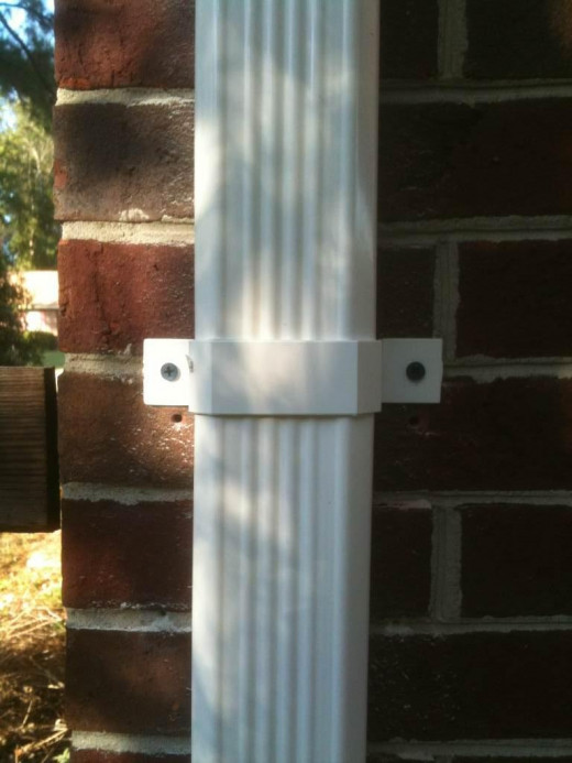 "Downspout bracket secured using 3/16"" anchor screws."