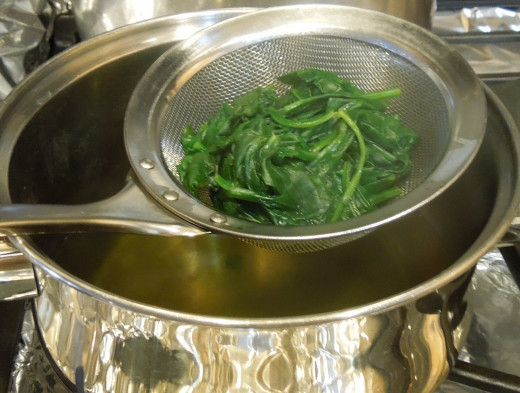 Draining cooked spinach