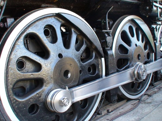 The wheels on the steam locomotive are huge