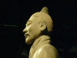 The sideview shows his simple top-knot hairstyle
