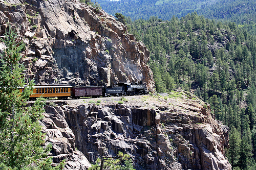 The current day Durango & Silverton Narrow Gauge Railroad traverses along the steep canyon walls hundreds of feet above the Animas River below.
