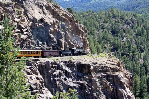 The current day Durango & Silverton Narrow Gauge Railroad traverses along the steep canyon walls hundreds of feet above the Animas River below.