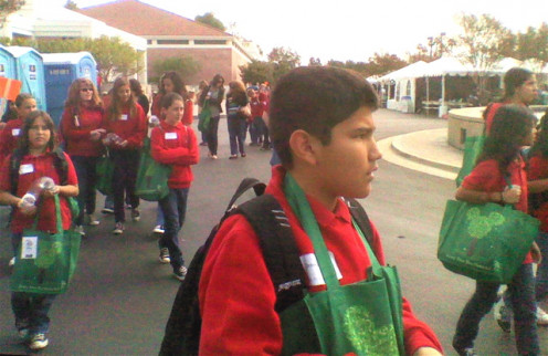 5th graders walking to their next activity. The green bag around this student's neck holds a T-shirt, educational materials, and additional items from some of the booths.