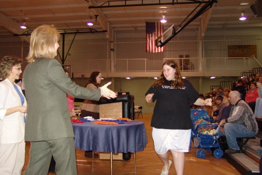 A student walks up to receive her award for a school-wide writing and art competition.