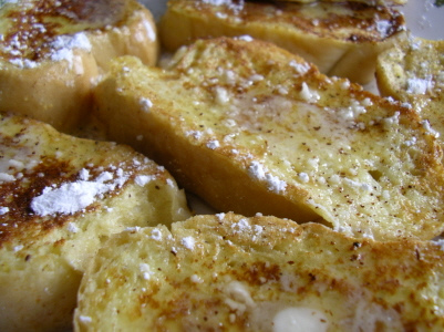 Soaked in beaten eggs, milk and spices, French toast is fried in butter and dusted with powdered sugar as a high caloric, delicious treat.