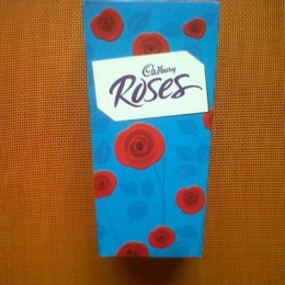 Cadbury Roses come in a distinctive blue box with pictures of red roses.