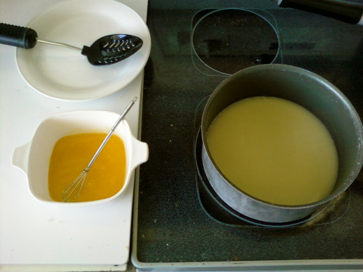 The cream mixture is heating on the stove, with the egg yolks ready to be added.