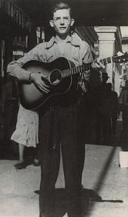 Hank Williams playing guitar on a sidewalk in Montgomery Alabama. (Copyright:1938-Photograph from the Alabama Department of Archives and History)