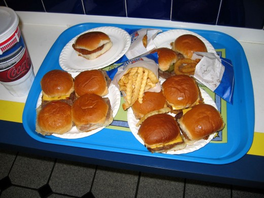 A tray of White Castle hamburgers, a chicken sandwich,  fries, onion rings, and a large soft drink.