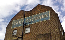 "The words ""Take courage"" on a building."