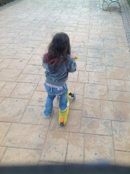 Riding her yellow Mini Micro Scooter and loving it!