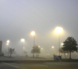 Fog scatters the yellow light of these parking lot lamps in much the same way as the atmosphere scatters the blue light from the Sun's rays.