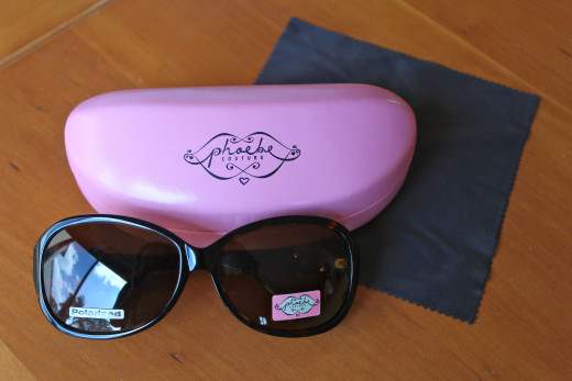 Boxy pink case and polishing cloth accompany these stylish Phoebe Couture sunglassess.