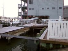 THE GRAY HOUSE IN THE BACK ROUND OF PHOTO HAS THE BOTTOM SIDE BLOWN OUT FROM THE SURGE OF THE WATER.