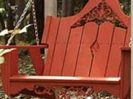 wide slat porch swing in redwood color and hanging by a chain