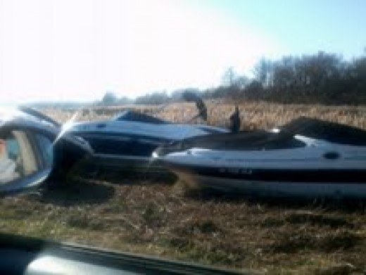 THERE ARE SO MANY BIG AND SMALL BOATS WASHED INTO THE MARSHLANDS.  THEY ARE EVEN IN THE WOODS TO THE RIGHT OF PHOTO.