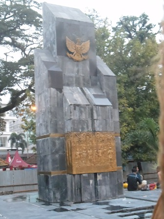 Clearer image of the national monument. Background: People renovating the monument