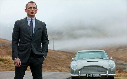 Screen shot of Bond (Craig) standing alongside an Aston Martin in Skyfall