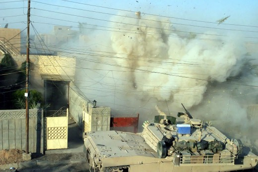 A US Marine Corps (USMC) Marine M1A1 Abrams Main Battle Tank (MBT), 2nd Tank Battalion (BN), fires its main gun into a building to provide suppressive counter fire against insurgents who fired on other USMC Marines during a fire fight in Fallujah, Al